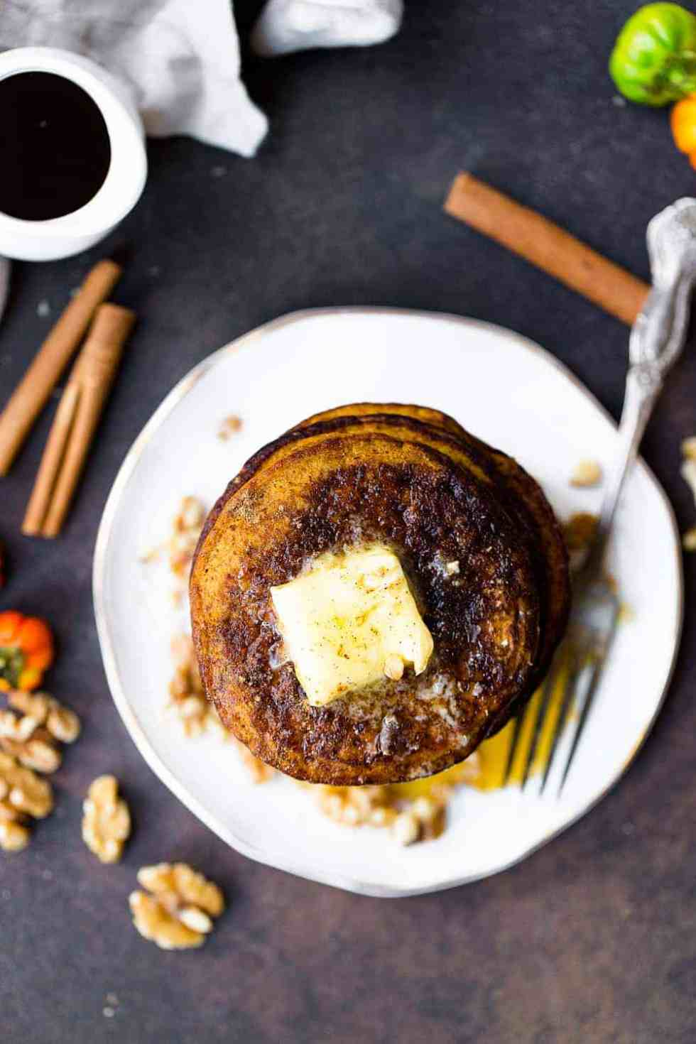 coconut flour pumpkin pancakes on a white plate with butter on top
