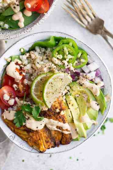 This recipe for Whole30 Fish Taco Bowls will leave you wanting more! Healthy whole30 fish taco bowl that is served on a bed of lettuce and cauliflower rice, topped off with a creamy chipotle sauce! Only 10 minutes to prepare! whole30 meal plan. Easy whole30 dinner recipes. Whole30 recipes. Whole30 lunch. Whole30 meal planning. Whole30 meal prep. Healthy paleo meals. Healthy Whole30 recipes. Easy Whole30 recipes. Easy whole30 dinner recipes...
