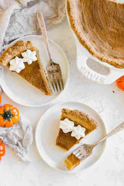 slices of pumpkin pie on white plates with whipped cream on top
