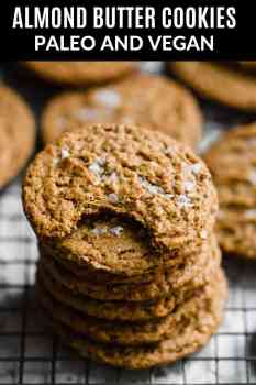 a stack of almond butter cookies on a wire rack with flaked sea salt on top