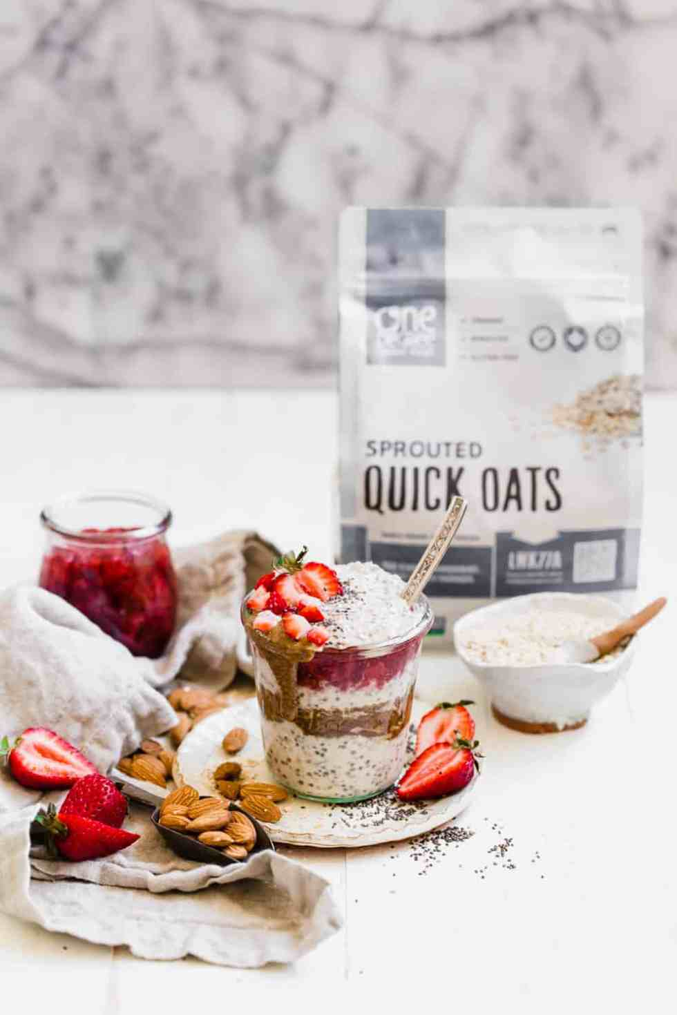 overnight oats in a glass jar with a spoon inside and fresh strawberries