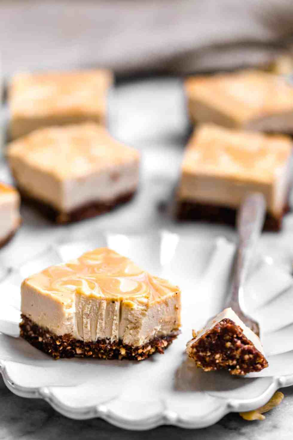 a peanut butter cheesecake bar on a white plate with a fork on the side