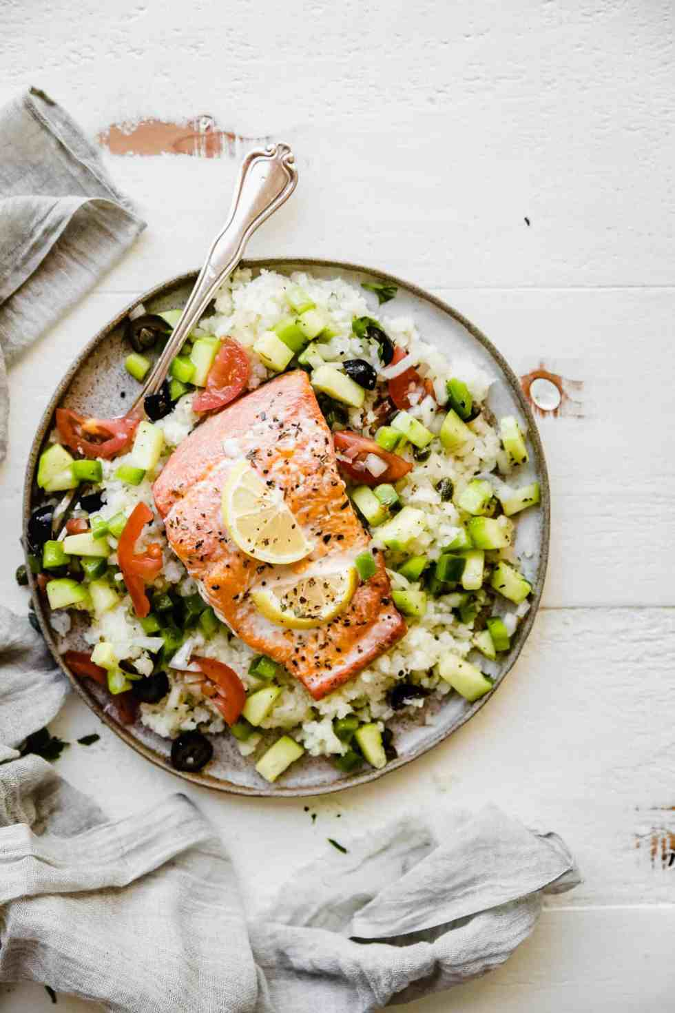 Whole30 Greek salmon on a plate with cauliflower rice and salad