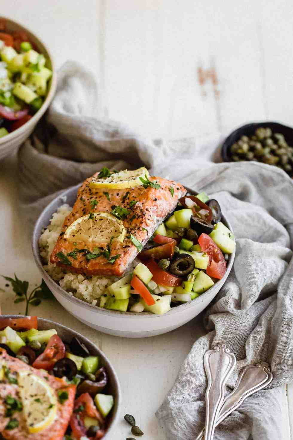 side shot of Whole30 greek salmon in a bowl with greek salad