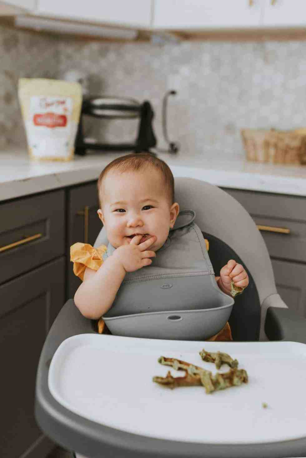 baby eating bone broth waffles in a high chair