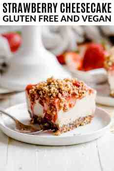 a slice of vegan strawberry cheesecake on a white plate with a fork