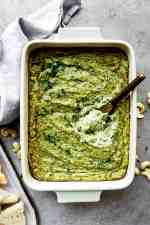 vegan spinach artichoke dip in a baking dish with a small knife inside