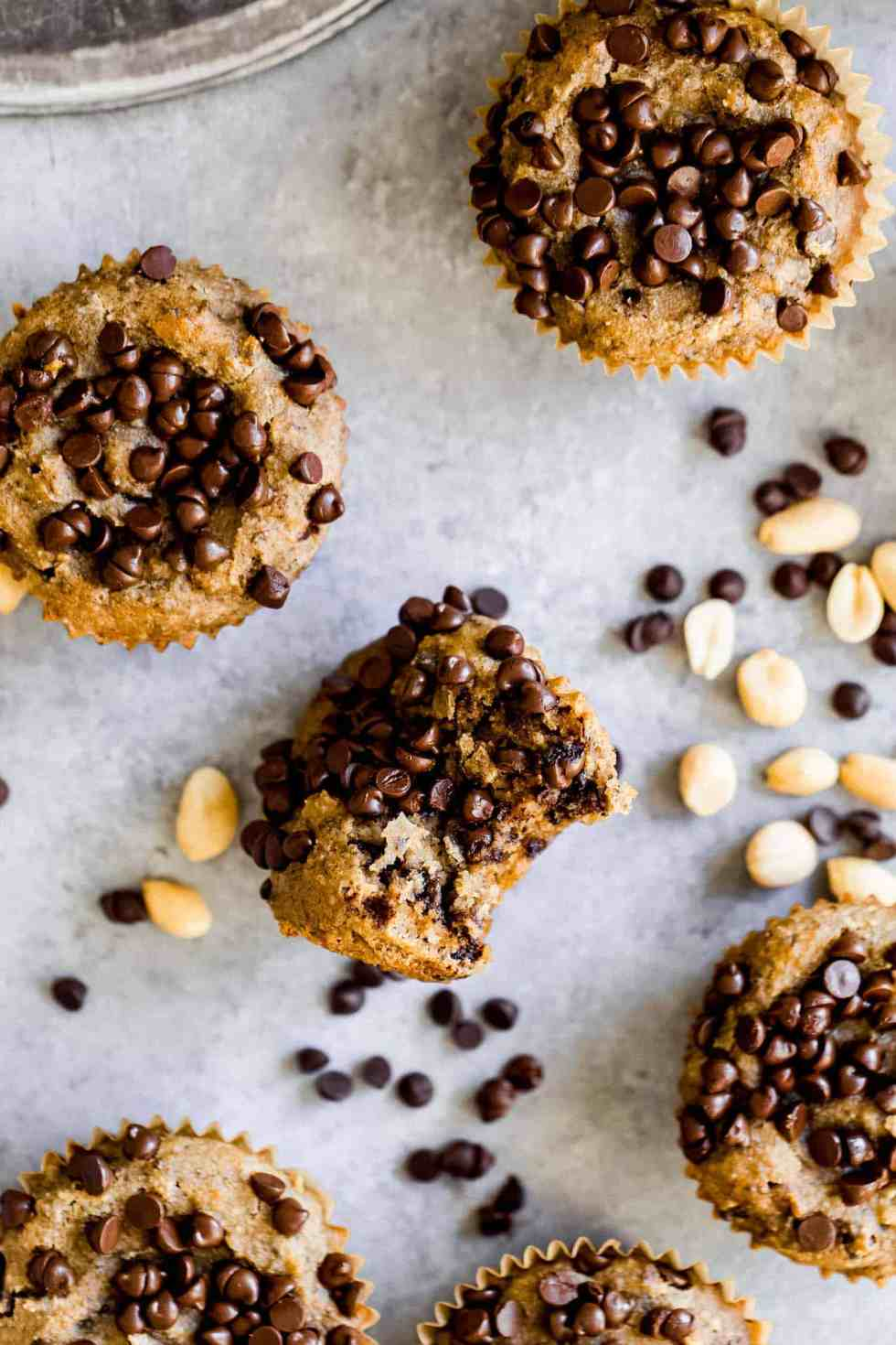 muffins with dark chocolate chips on top on a grey board