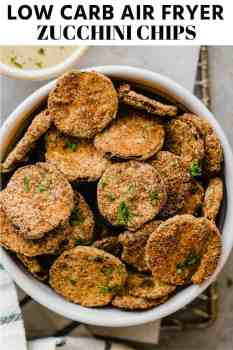 air fryer zucchini chips in a bowl with dipping sauce on the side