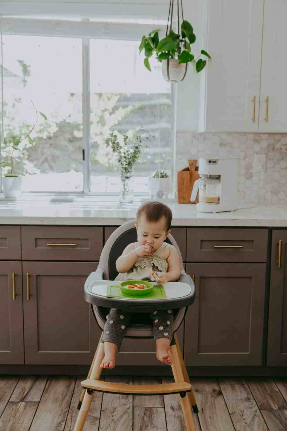 baby eating food in a gray and white high chair