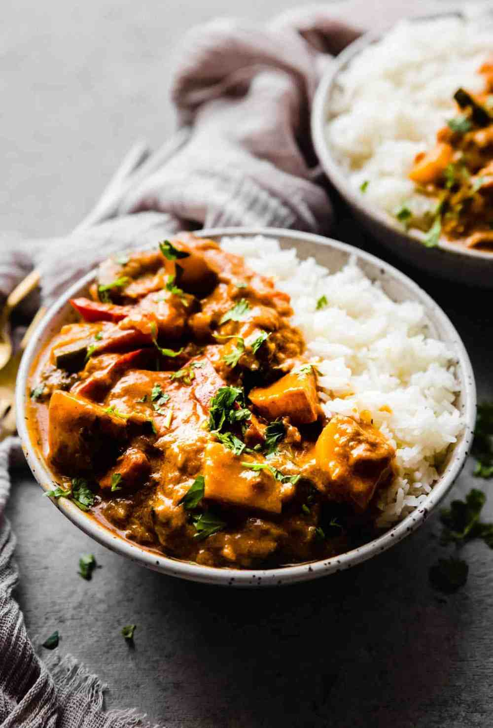 red curry in a bowl with white rice and cilantro on top