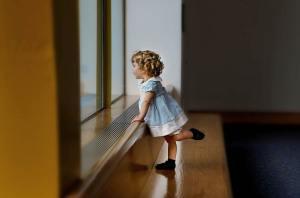 child next to a window.
