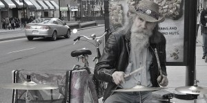 An old man playing the drums in the street.