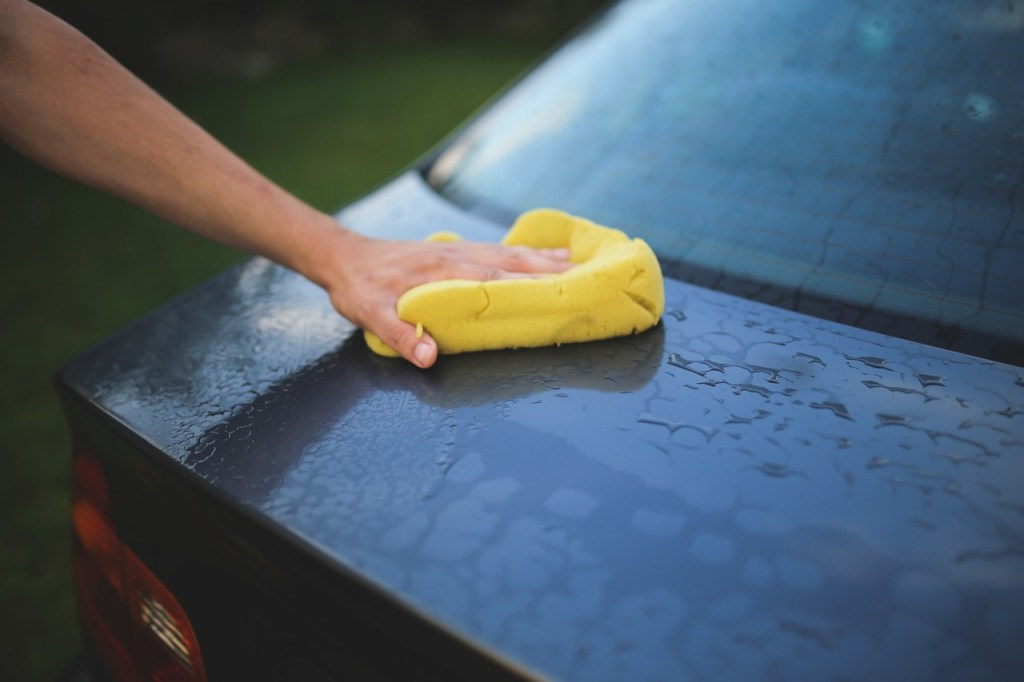 A man cleaning a car. You should do this before transporting your car from Chicago to LA.