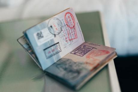 An open passport with plenty of stemps inside it.
