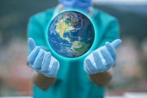 nurse holding a globe in protective gloves