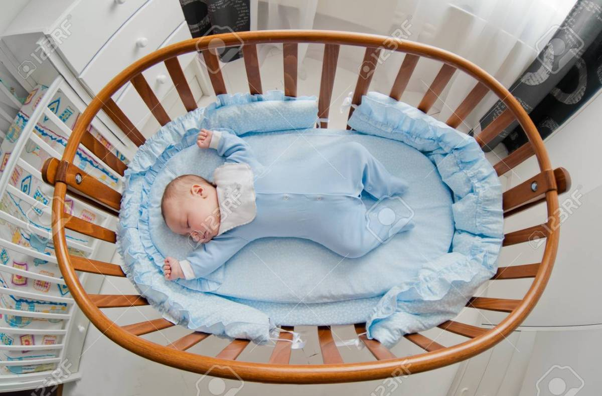 Baby's restful sleep. Newborn baby in a wooden crib. The baby sleeps in the bedside cradle.