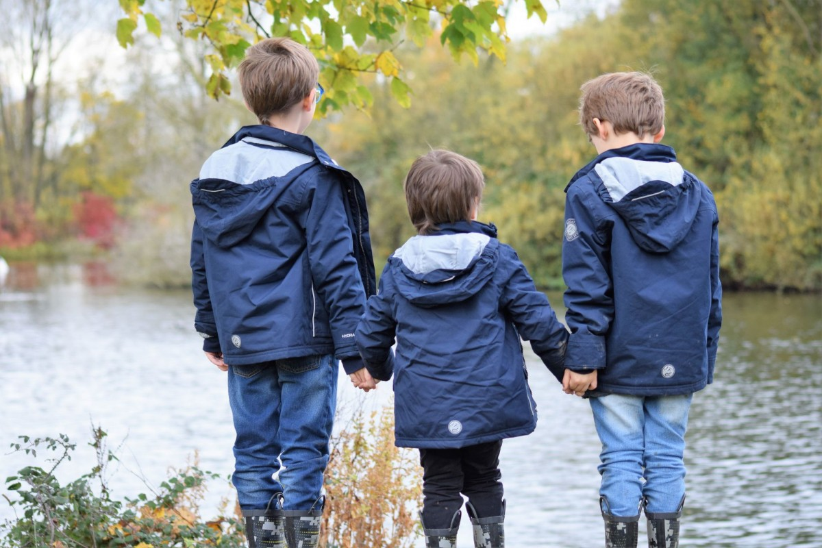 3 brothers looking over a lake holding hands