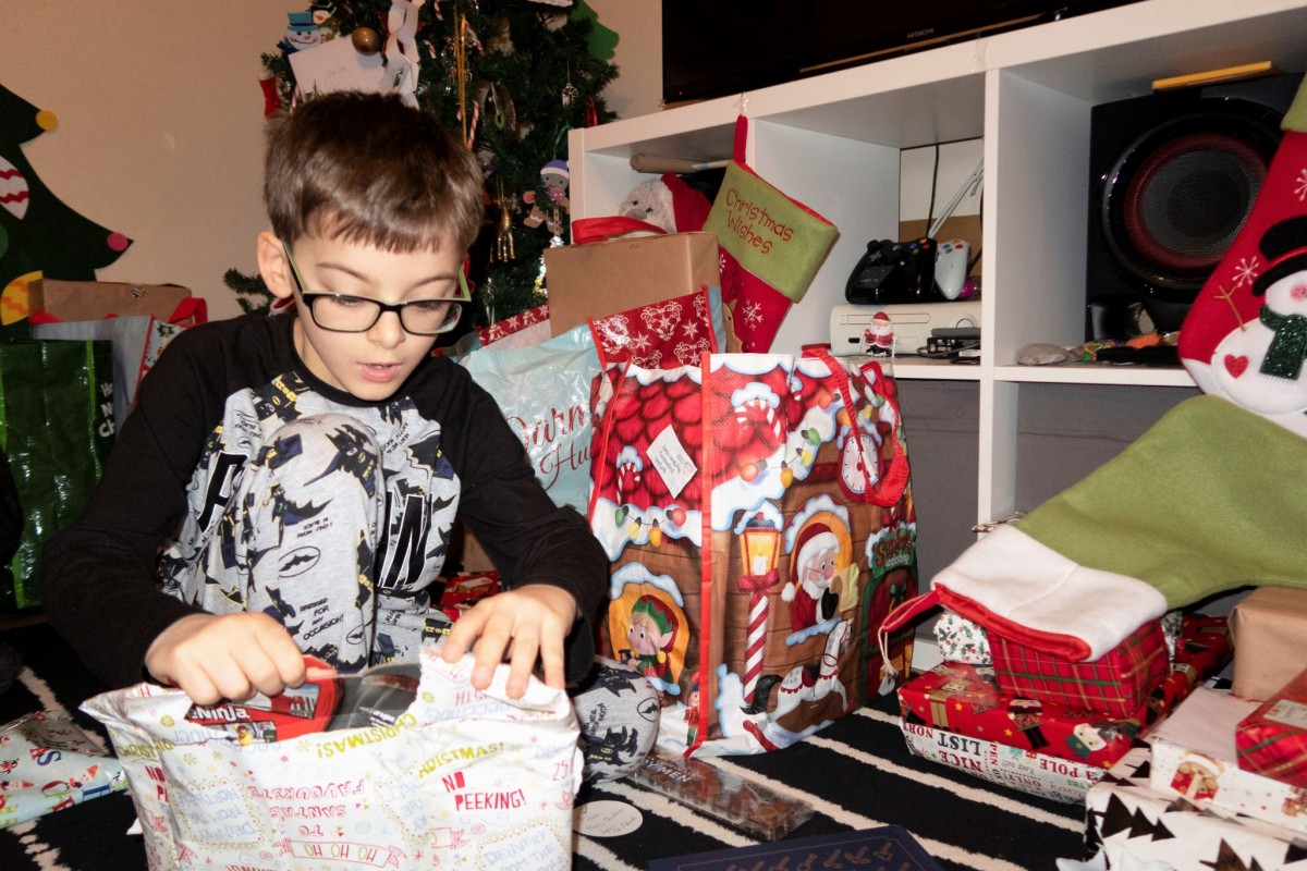boy child aged 7 unwrapping a christmas gift. Surrounded by christmas presents and gift bags