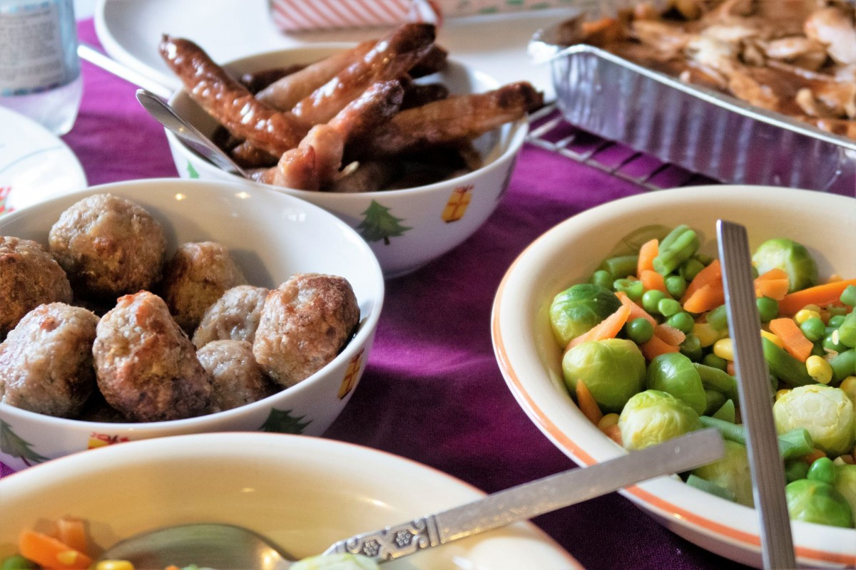 various vegetables in bowls, as well as a bowl full of chipolata sausages and another bowl of stuffing balls from MuscleFoods