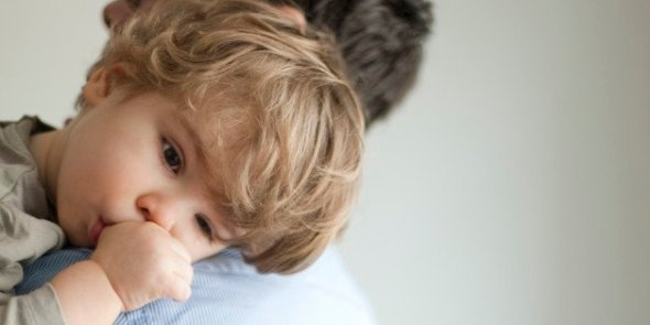 Toddler boy resting head on father's shoudler positive parenting