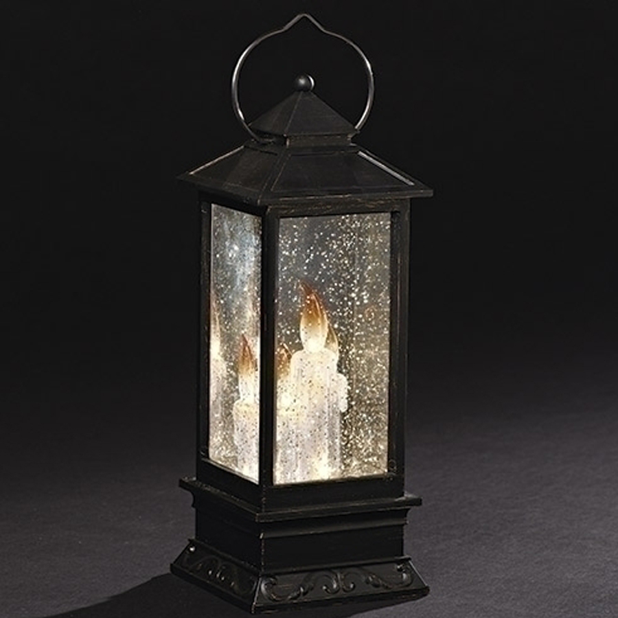 Large black lantern with candles and lights inside. Automatic swirl glitter