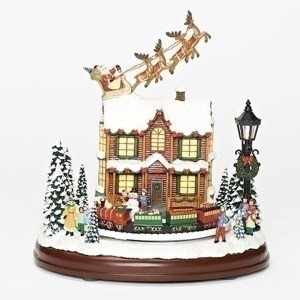 Santa and Reindeer over rooftop with lighted house and revolving train musical