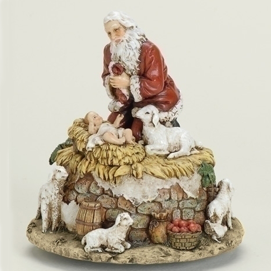 Santa kneeling by manger with animals