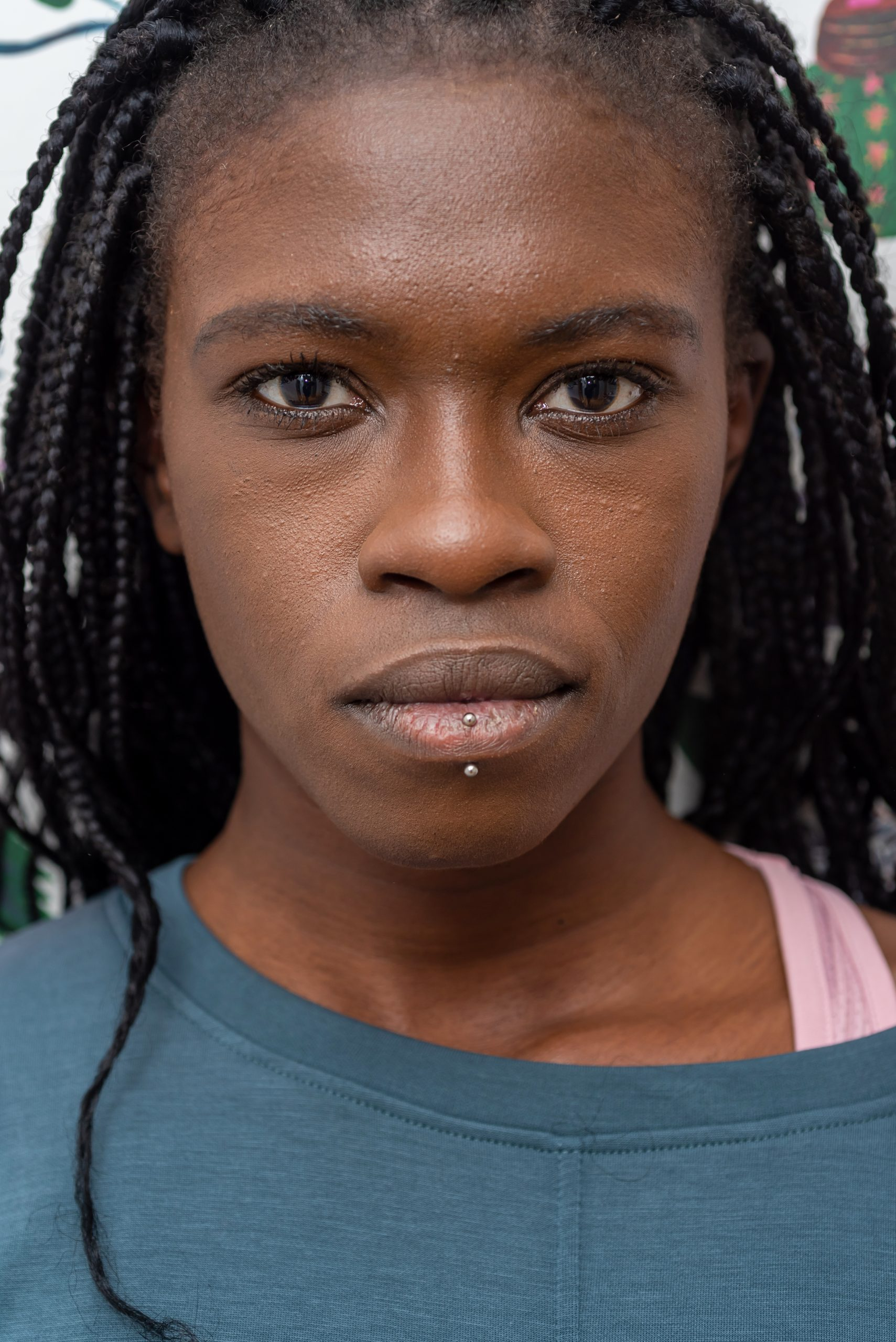 Headshot of determined African American female with black braids and piercing looking at camera