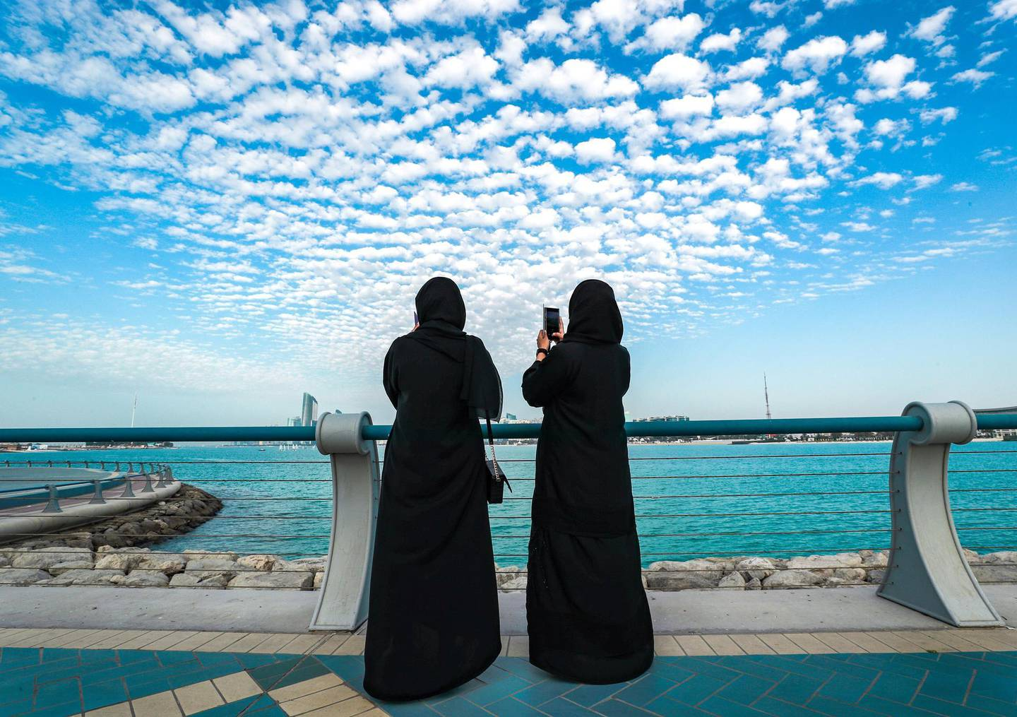 Abu Dhabi, United Arab Emirates, March 3, 2021.  Friends enjoy the view of tiny cotton ball like clouds at the Corniche before sunset.  Victor Besa / The National Section:  NA For:  Big Picture/Stock Images/Standalone