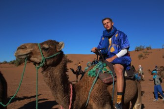 "Michael ""Big Mike"" Collett riding on the back of a dromedary camel Camelus dromedarius in the Sahara Desert in Morocco on Semester at Sea Spring 2016 Photo Credit Zack Neher"