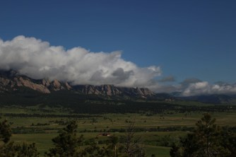 The Flatirons and the Rocky Mountains covered by clouds in Boulder Colorado Photo Credit Zack Neher
