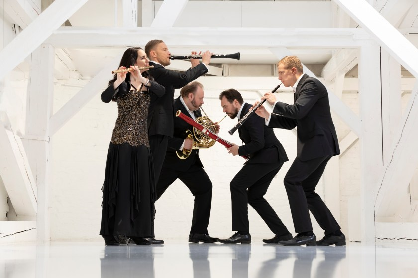 Five woodwind players strike a dance pose in a white loft.