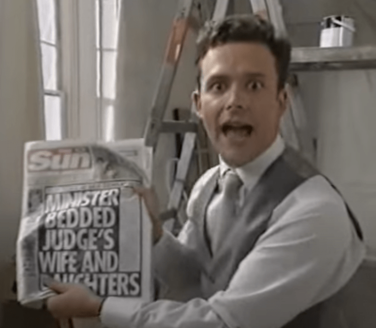 Figaro as a modern butler holds the Sun tabloid.