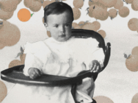 Vladimir Nabokov, age 2, in high chair against a backdrop of oranges