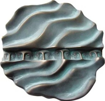 Bronze medallion of ocean waves with people peering through a slit