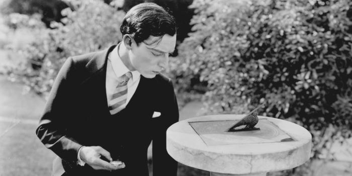 Buster Keaton checks his watch against a sundial