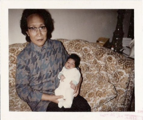 Photo from the 1970s of an Asian grandma sitting on a couch holding an infant.