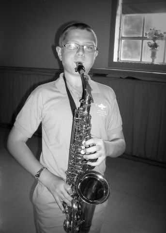 Student having fun trying a saxophone for the first time.