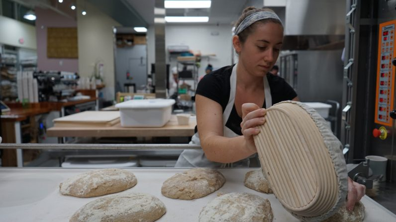 Naomi placing the dough before its put into the oven. (Credit: Roshan Nebhrajani/The New Tropic)