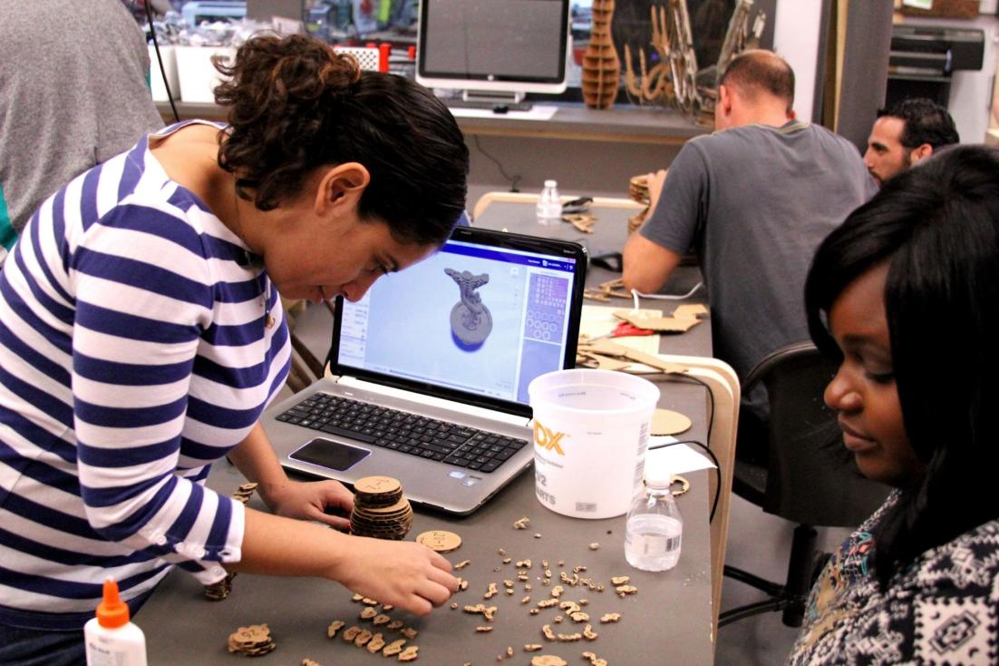 Fannie Torres (left) and Diana Eloi (right) working on their laser-cut upcycled Groot at Moonlighter Makerspace. (Courtesy of Danielle Ungermann)