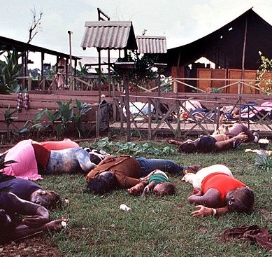 Jonestown Massacre, where 912 people died because they followed Jim Jones. A child, one of hundreds, is in between parents who murdered. (Credit Tim Chapman, Courtesy of History Miami)
