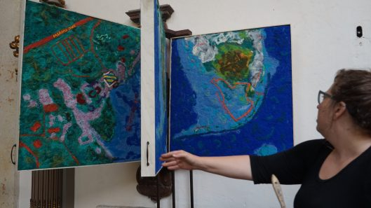Artist Lucinda Linderman displays the panels which showcasing handmade maps tracing the levels of sea level rise in 50 years.