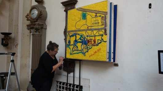 Artist Lucinda Linderman putting maps up in the main house hallways.