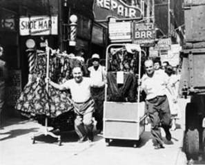 Workers move clothes in the garment district.