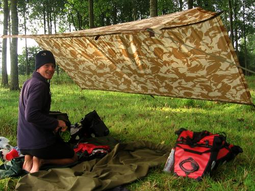 Camped beneath a tarp in a forest