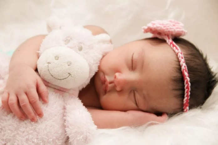 A newborn baby girl sleeping peacefully while holding her teddy bear