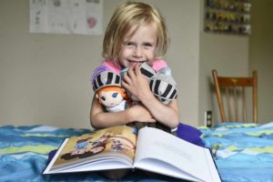 Girl with Night Knight book and dolls