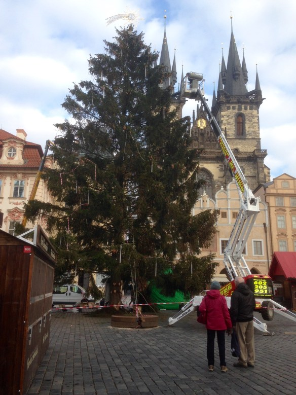 The Old Town Square is getting ready for the Christmas Markets to open this weekend. One of the highlights each year is the lighting of the Christmas tree. The lighting ceremony has been canceled this year because of terrorism concerns. The tree will be lit, but the time won't be publicized. We happened by after lunch today to see them getting the tree ready. Normally this square is the most wide-open in the city and continually features street performers. For the Christmas Markets, though, the area will be filled with stalls such as the one at left, creating an outdoor mall offering copious quantities of hot meat, trdlo pastries, mulled wine and grog, and gifts and crafts of all kinds. Should be magical.