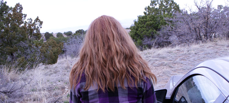 My friend Hannah standing by her car and looking out into the vast wilderness of the Sandia Mountains.